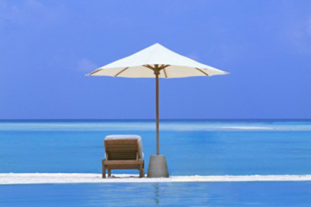 Image of blue sky and ocean with umbrella snd chair on the beach.