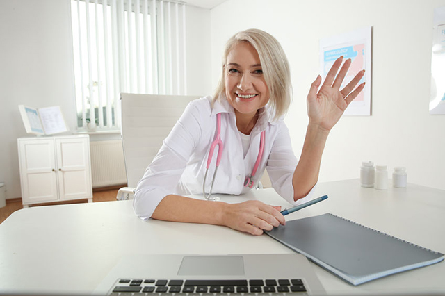 Image of smiling doctor in her surgery waving to patient on-line during onine consultation.